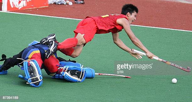 China's Liu Xian Tang collides with Malaysia's goalkeeper Mohammad Fairus Md Wanazir during their match for third and fourth place at the Asia Cup...