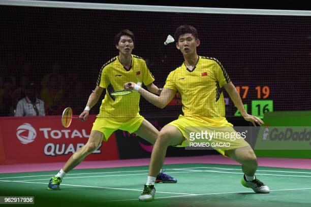 China's Liu Yuchen hits a return against Japan's Yuta Watanabe and Keigo Sonoda as his teammate Li Junhui looks on during their mendouble final match...