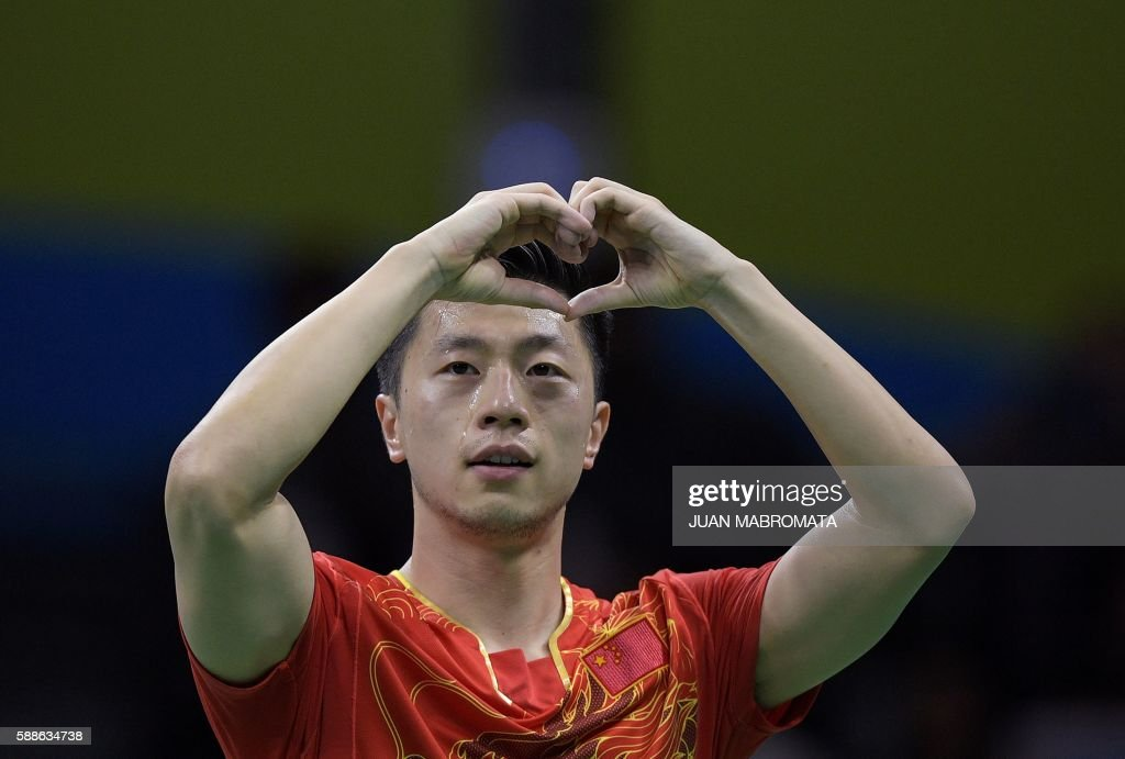 TOPSHOT - China's Ma Long celebrates beating China's Zhang Jike in their men's singles final gold medal table tennis match at the Riocentro venue during the Rio 2016 Olympic Games in Rio de Janeiro on August 11, 2016. / AFP PHOTO / Juan Mabromata