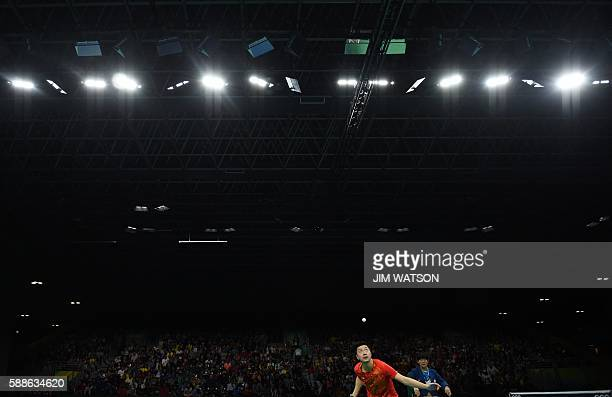 China's Ma Long eyes the ball as he serves against China's Zhang Jike in their men's singles final gold medal table tennis match at the Riocentro...