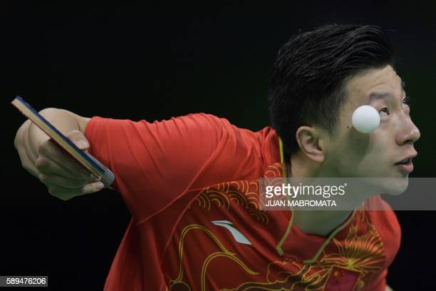 TOPSHOT China's Ma Long eyes the ball as he serves to Britain's Liam Pitchford during the men's team quarterfinal table tennis match at the Riocentro...