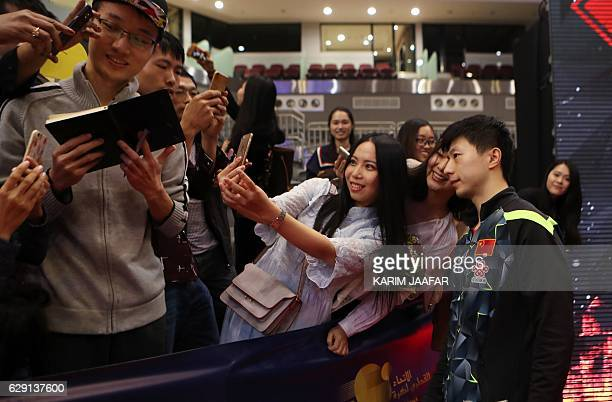 China's Ma Long poses with fans after winning his men's singles table tennis final match on December 11 during the Qatar 2016 ITTF World Tour Grand...