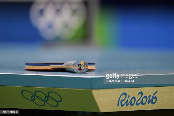 China's Ma Long's racket with his own picture on the end is seen on the table between points against Nigeria's Quadri Aruna in their men's singles...