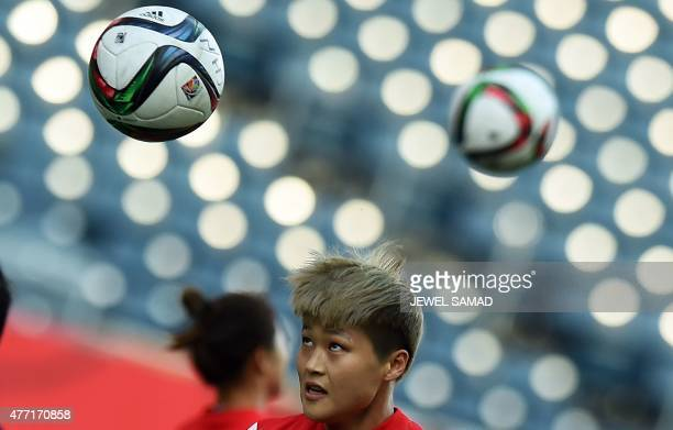 China's midfielder Ma Jun heads a ball during a training session at the Winnipeg Stadium on the eve of their Group A football match of the 2015 FIFA...
