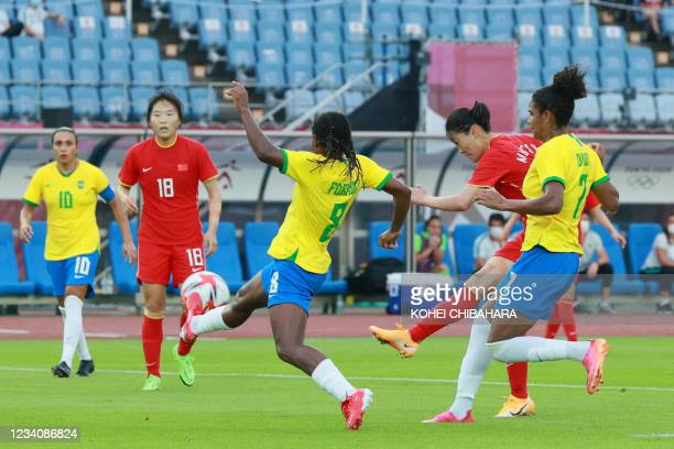 China's midfielder Miao Siwen takes a shot as she is marked by Brazil's midfielder Formiga during the Tokyo 2020 Olympic Games women's group F first...