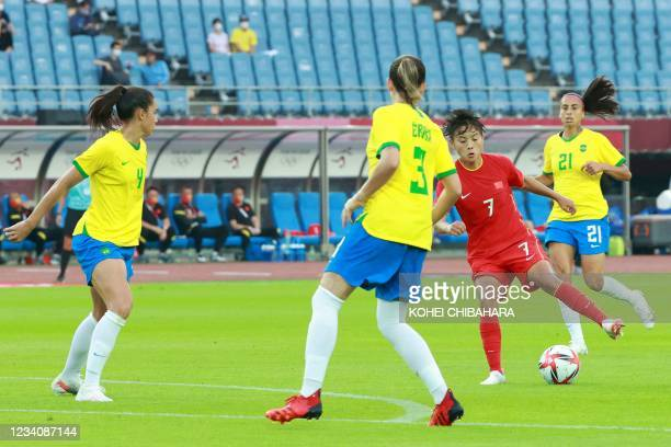 China's midfielder Wang Shuang controls the ball as she is marked by Brazil's defender Erika and Brazil's defender Rafaelle during the Tokyo 2020...
