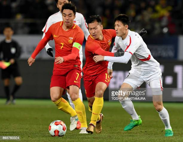 China's midfielder Wu Xi fights for the ball with North Korea's defender Jang KukChol during the men's football match between China and North Korea...