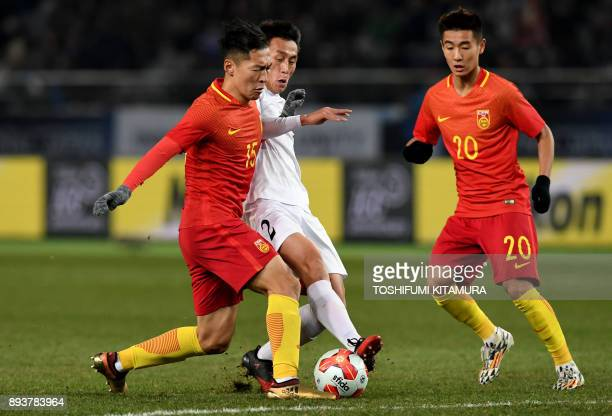 China's midfielder Wu Xi fights for the ball with North Korea's defender Sim HyonJin during the men's football match between China and North Korea at...