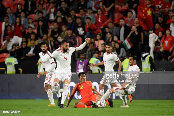 China's midfielder Zhi Zheng vies for the ball with Iranian players during the 2019 AFC Asian Cup quarterfinal football match between China and Iran...