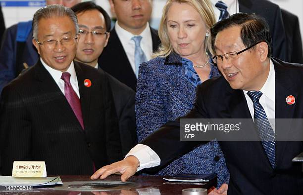 China's Minister of Science and Technology Wan Gang introduces a cooking and heating stove on exhibition to US Secretary of State Hillary Clinton and...