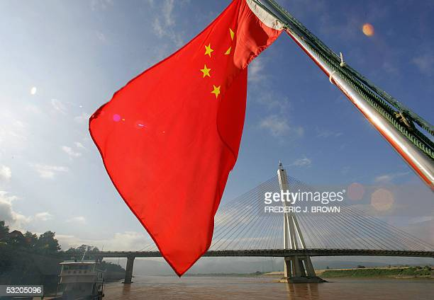 China's national flag flies from the back of a ship sailing down the Mekong River downstream past the Xishuangbanna Great Bridge in Jinghong 06 July...