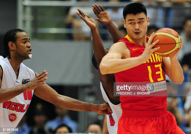 China's NBA star Yao Ming looks for a pass as Angola's Joaquim Gomes guards during their Stankovic Cup basketball game in Hangzhou on July 19 2008 in...