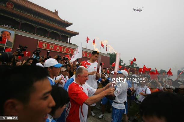 China's NBA star Yao Ming passes on the Olympic flame to Hein Verbruggen chairman of the International Olympic Committee Coordination Commission in...