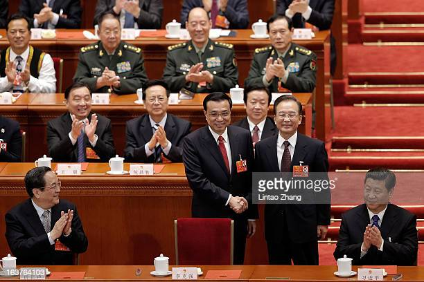 China's newlyelected Premier Li Keqiang shakes hands with former Chinese Premier Wen Jiabao near Chinese President Xi Jinping during the fifth...