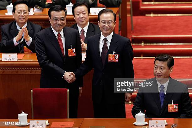 China's newly-elected Premier Li Keqiang shakes hands with former Chinese Premier Wen Jiabao near Chinese President Xi Jinping during the fifth...