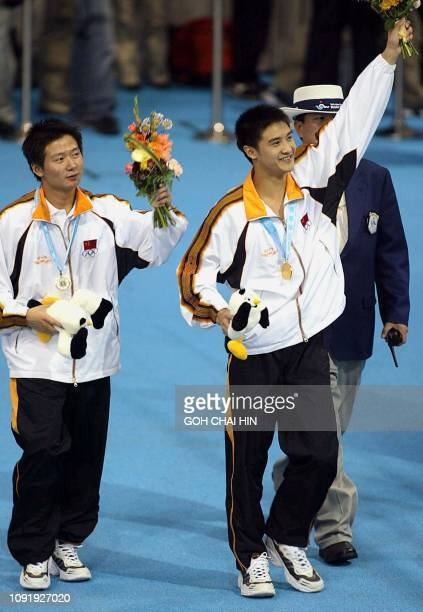 China's Olympic and world champion Tian Liang and teammate Xu Xiang celebrate after receiving their medals in the men's 10m platform final at the...