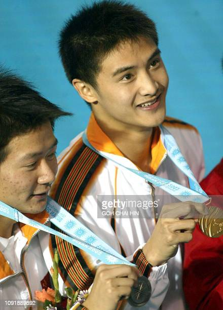China's Olympic and world champion Tian Liang shows off his gold medal while teammate Xu Xiang with his silver medal in the men's 10m platform final...