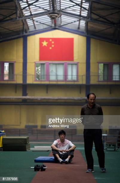 China's Olympic champion 110-meter hurdler Liu Xiang rests as his coach Sun Haiping walks past during a training session at the National Training...