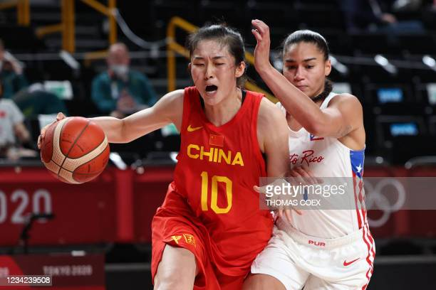 China's Pan Zhenqi dribbles the ball past Puerto Rico's Tayra Melendez in the women's preliminary round group C basketball match between China and...