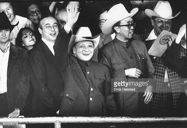 China's paramount leader Deng Xiaoping waving, wearing cowboy hat presented to him by his hosts, attending rodeo, entourage-in-tow, stop on his state...