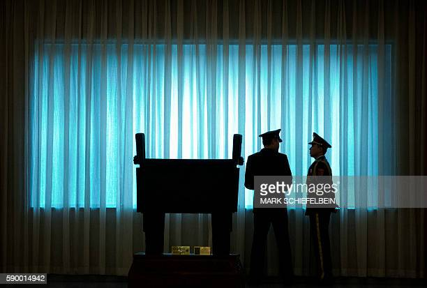 TOPSHOT China's People's Liberation Army officers stand in front of a window before a welcome ceremony for US Army Chief of Staff General Mark Milley...