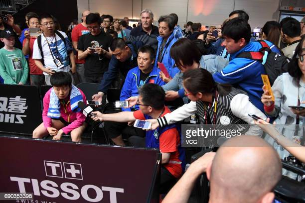China's player Mu Zi receives interviews as coach Li Sun sits behind her after women qualification on day 2 of 2017 World Table Tennis Championships...