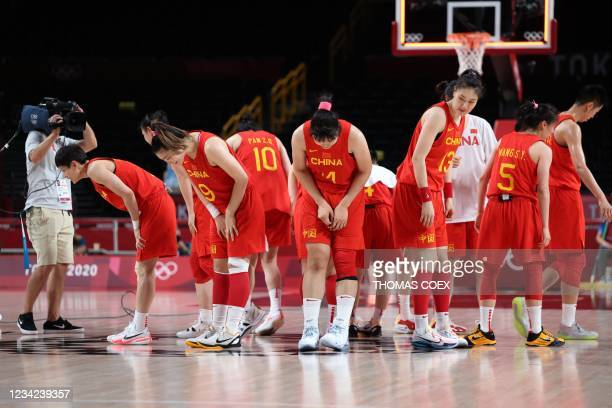 China's players bow down after their victory in the women's preliminary round group C basketball match between China and Puerto Rico during the Tokyo...