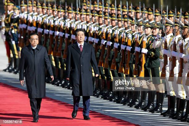 China's Premier Li Keqiang accompanies Japanese Prime Minister Shinzo Abe to view an honour guard during a welcoming ceremony outside the Great Hall...