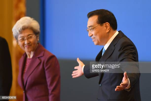 China's Premier Li Keqiang gestures to journalists as National People Congress spokeswoman Fu Ying looks on as they arrive for a press conference...