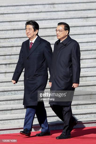 China's Premier Li Keqiang invites Japanese Prime Minister Shinzo Abe to view an honour guard during a welcoming ceremony outside the Great Hall of...