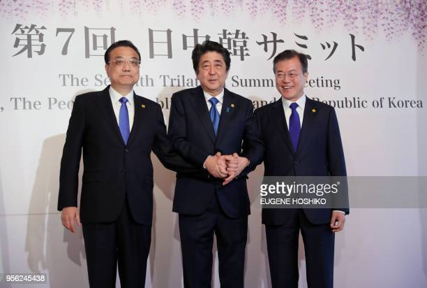 China's Premier Li Keqiang Japan's Prime Minister Shinzo Abe and South Korea's President Moon Jaein join hands as they pose for photos prior to the...