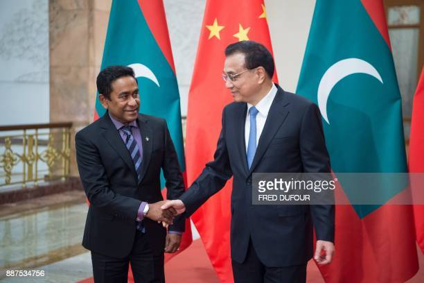 China's Premier Li Keqiang shakes hands with Maldives' President Abdulla Yameen at the Great Hall of the People in Beijing on December 7 2017 / AFP...