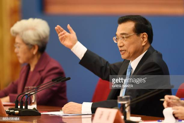 China's Premier Li Keqiang speaks beside National People Congress spokeswoman Fu Ying during a press conference after the closing session of the...