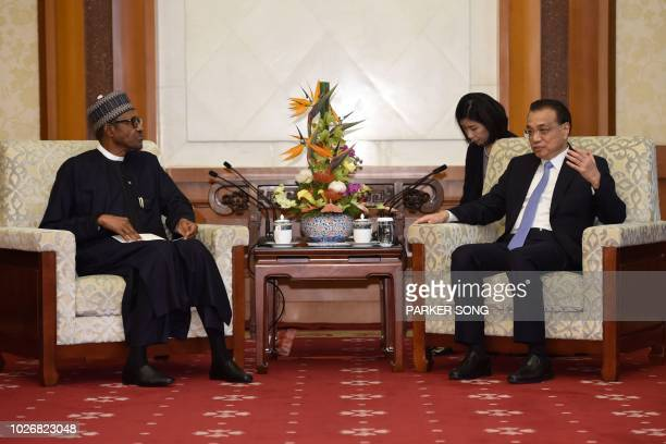 China's Premier Li Keqiang talks to Nigeria's President Muhammadu Buhari during their meeting at the Diaoyutai State Guesthouse in Beijing on...