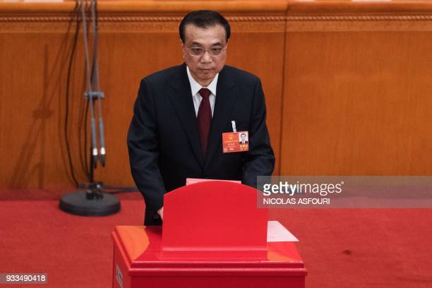 China's Premier Li Keqiang votes during the sixth plenary session of the National People's Congress at the Great Hall of the People in Beijing on...