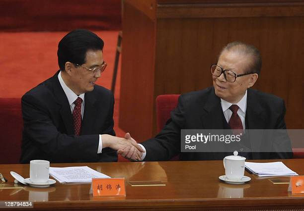 China's President Hu Jintao shakes hands with former president Jiang Zemin after making a speech at the Commemoration of the 100th anniversary of the...