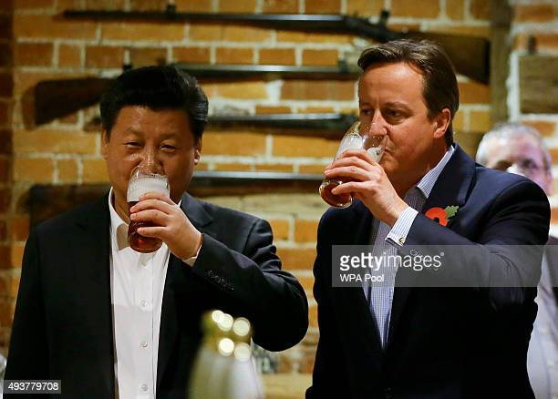 China's President Xi Jinping and Britain's Prime Minister David Cameron drink a pint of beer during a visit to the The Plough pub on October 22, 2015...