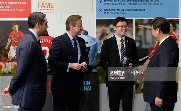 China's President Xi Jinping and Britain's Prime Minister David Cameron are introduced to former Manchester City player Sun Jihai by Manchester City...