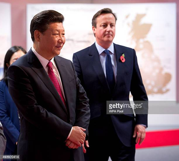China's President Xi Jinping and British Prime Minister David Cameron tour an exhibition of future developments at Manchester airport on October 23...