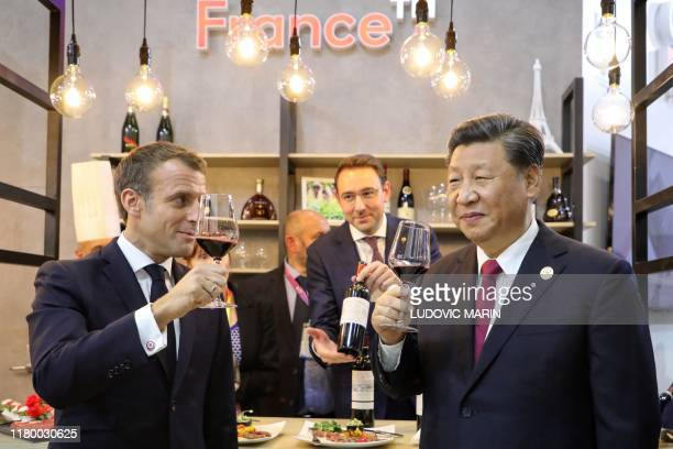 China's President Xi Jinping and French President Emmanuel Macron taste wine as they visit France's pavilion during the China International Import...