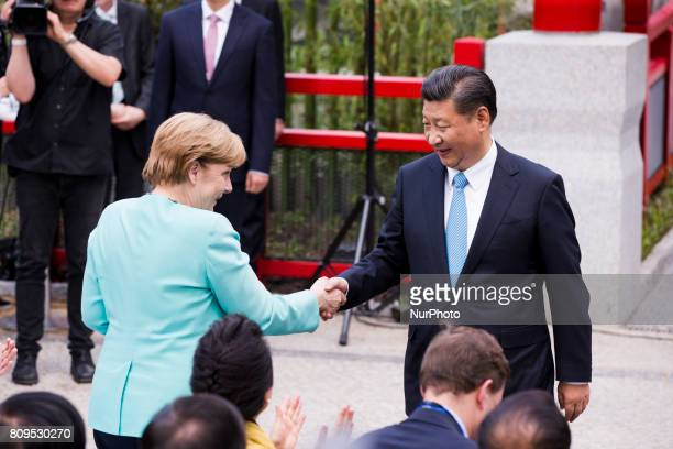 China's President Xi Jinping and German Chancellor Angela Merkel shake hands during the official welcoming ceremony for the panda couple Meng Meng...