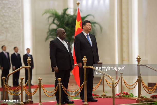 China's President Xi Jinping and Ghana President Nana AkufoAddo listen to anthems before to review the Chinese People's Liberation Army honour guard...