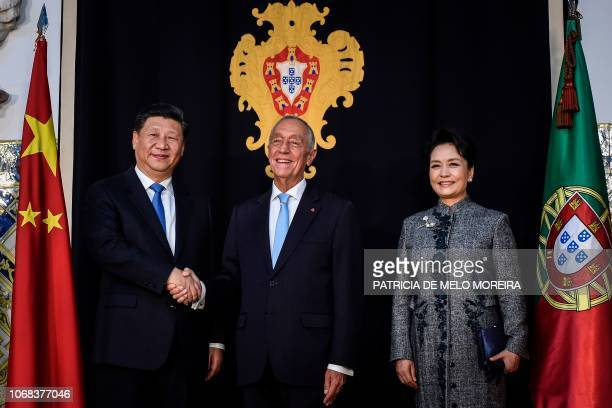 China's President Xi Jinping and his wife Peng Liyuan pose for a photo with Portugal's President Marcelo Rebelo de Sousa at Belem Palace in Lisbon on...