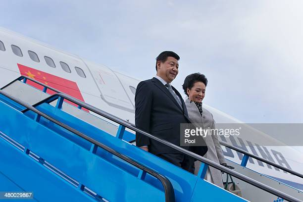 China's President Xi Jinping and his wife Peng Liyuan walk down the stairs from their aircraft prior to being greeted by King WillemAlexander of the...