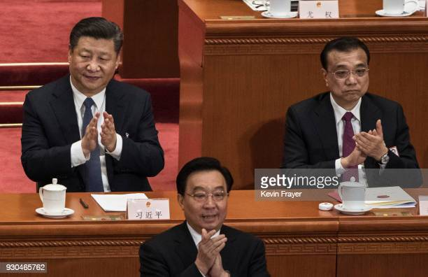 China's President Xi Jinping and Premier Li Keqiang applaud during a session of the National People's Congress after voting on a constitutional...