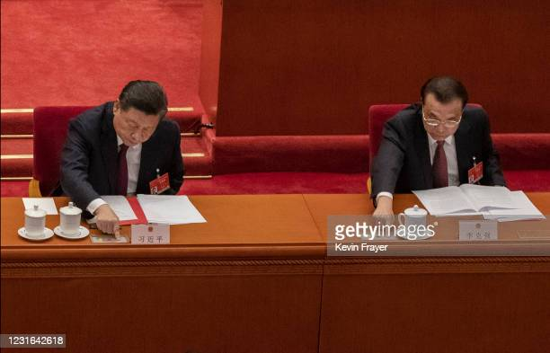 China's President Xi Jinping and Premier Li Keqiang, right, press a button to vote in favour of a resolution to overhaul Hong Kong's electoral...
