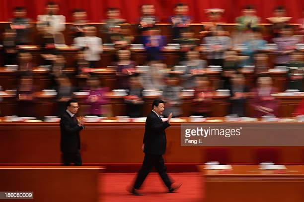 China's President Xi Jinping and Premier Li Keqiang wave to delegates as they arrive for the opening ceremony of the 11th National Women's Congress...