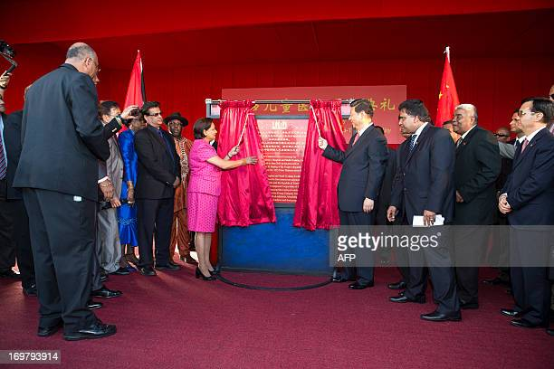 China's President Xi Jinping and Prime Minister of Trinidad and Tobago Kamla Persad-Bissessar unveil a plaque at the site of the Couva Children´s...