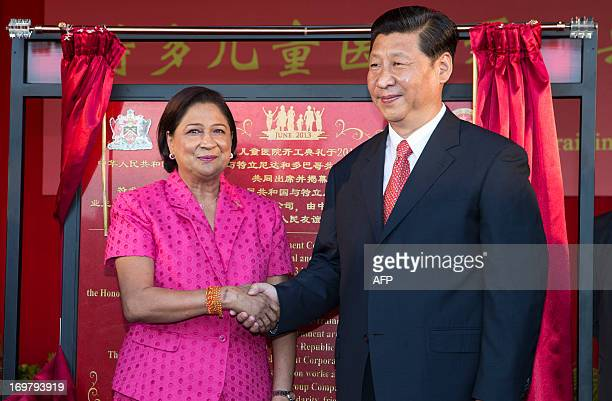 China's President Xi Jinping and Prime Minister of Trinidad and Tobago Kamla Persad-Bissessar shake hands at the site of the Couva Children´s...