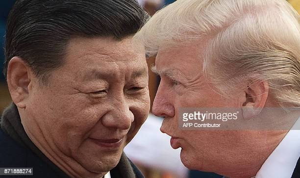 China's President Xi Jinping and US President Donald Trump attend a welcome ceremony at the Great Hall of the People in Beijing on November 9 2017 /...